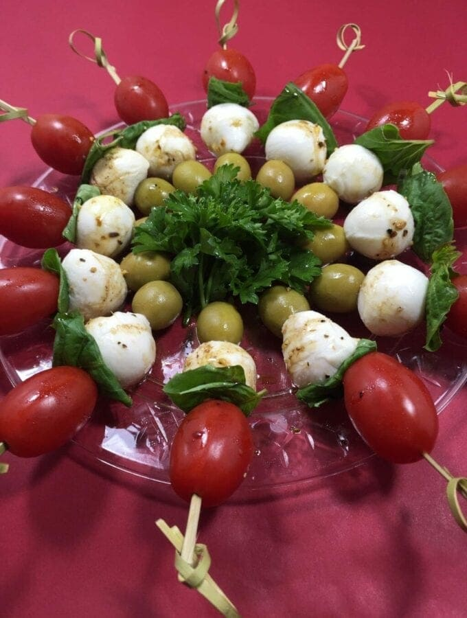 skewered tomatoes, basil, cheese and green olives on clear plate