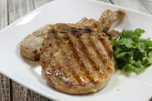 Grilled pork chops on a white plate