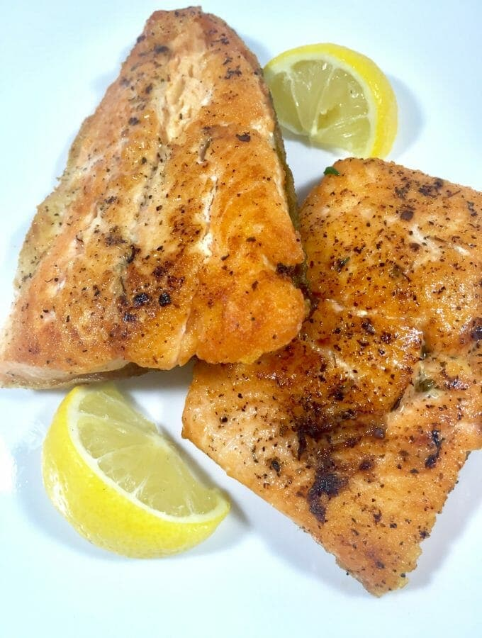 Baked Char salmon on a white plate with lemon slices