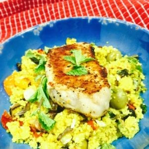 Curry Vegetable Couscous topped with a pork chop in a blue bowl.