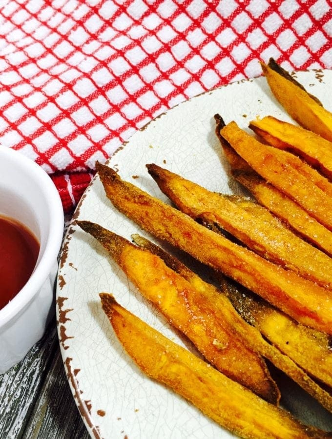 Sweet potato fries on a white plate along side ketchup in a white bowl