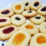 Baked jam filled shortbread cookies on a white plate