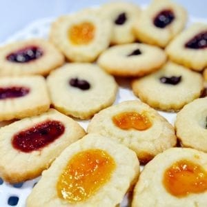 Jam filled shortbread cookies on a white plate