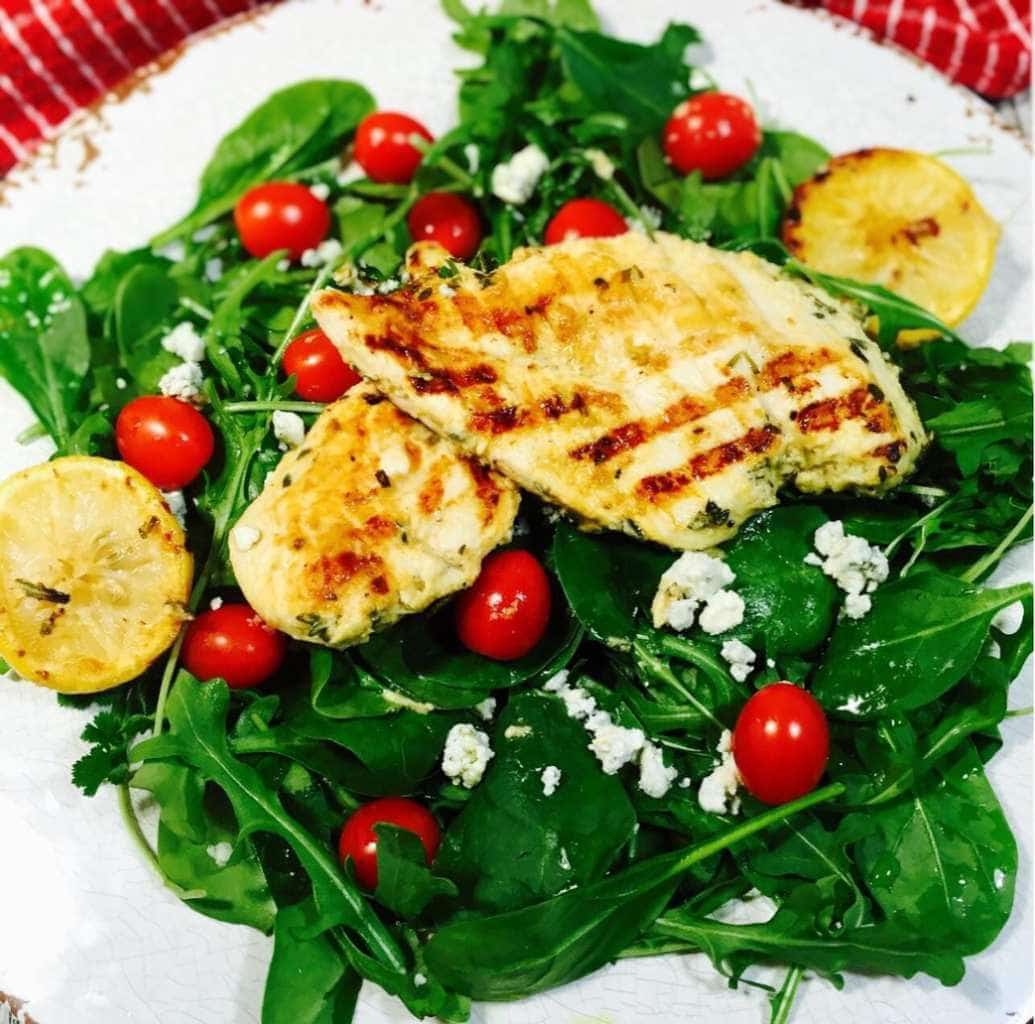 Grilled lemon chicken salad on a white plate