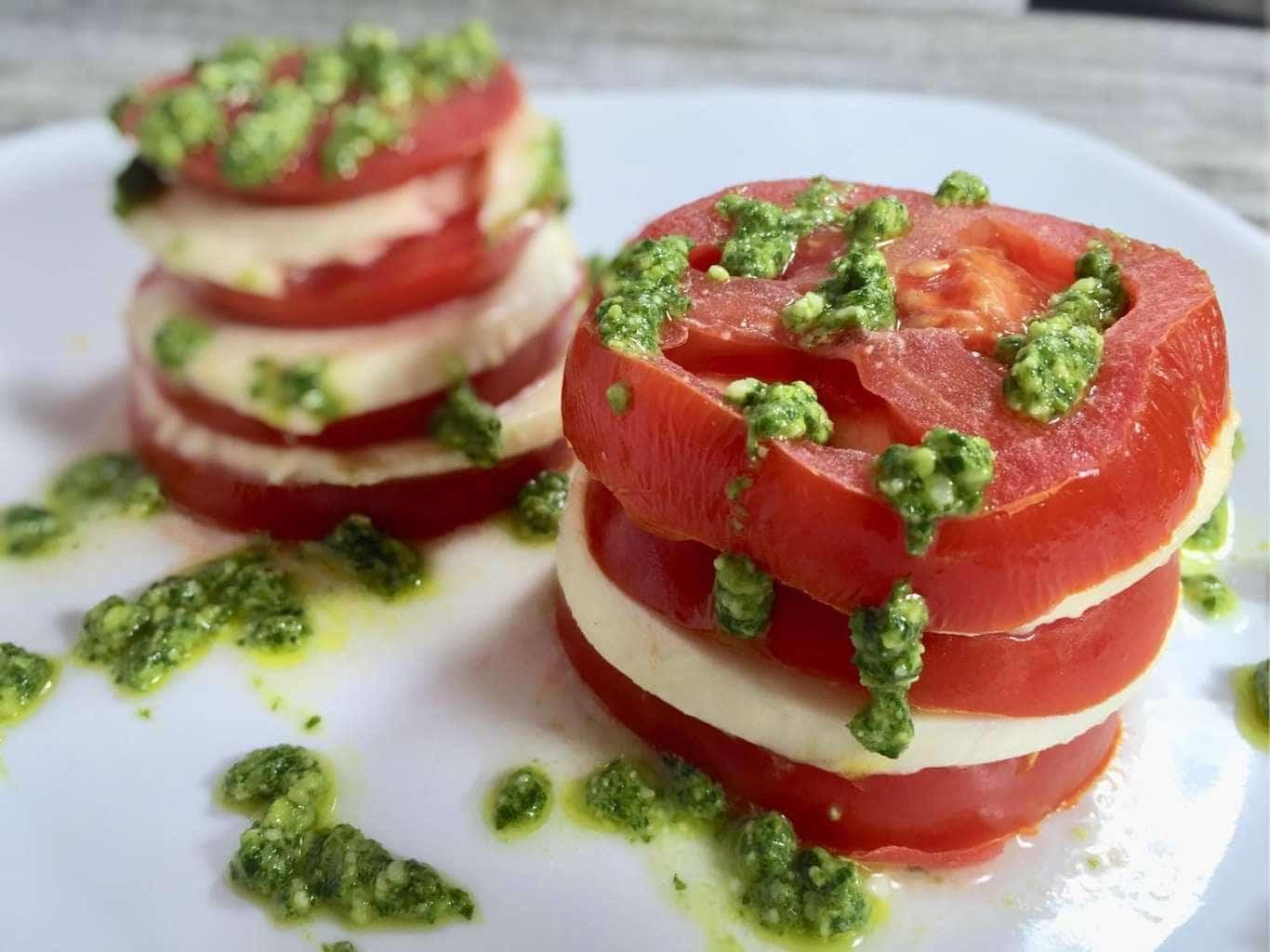 Stacked tomato salad with pesto on a white