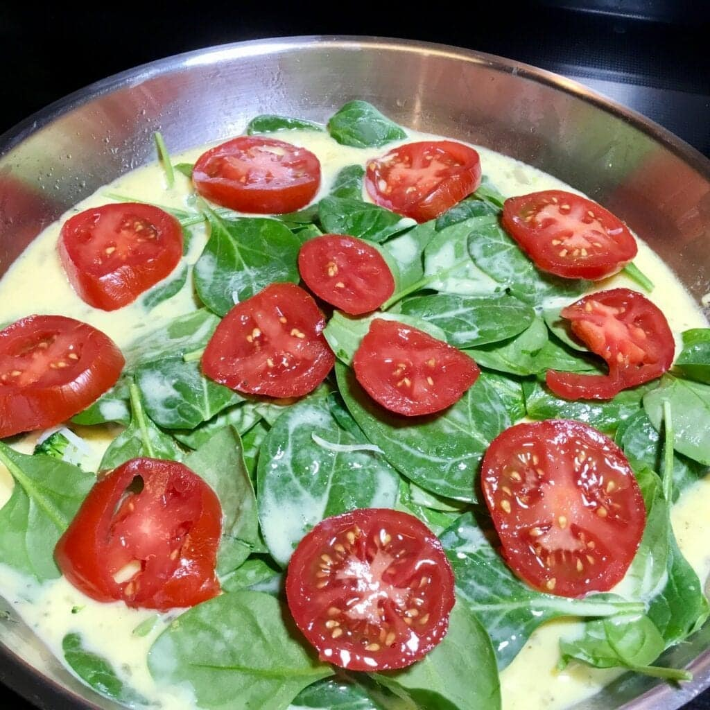 cooking a spinach and tomato frittata in a pan