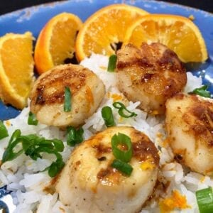 Sauteed sea scallops over rice with oranges