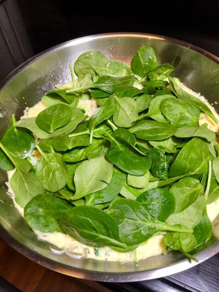 cooking a spinach frittata in a pan