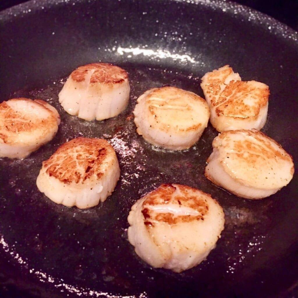 Sea scallops sautéing in a pan