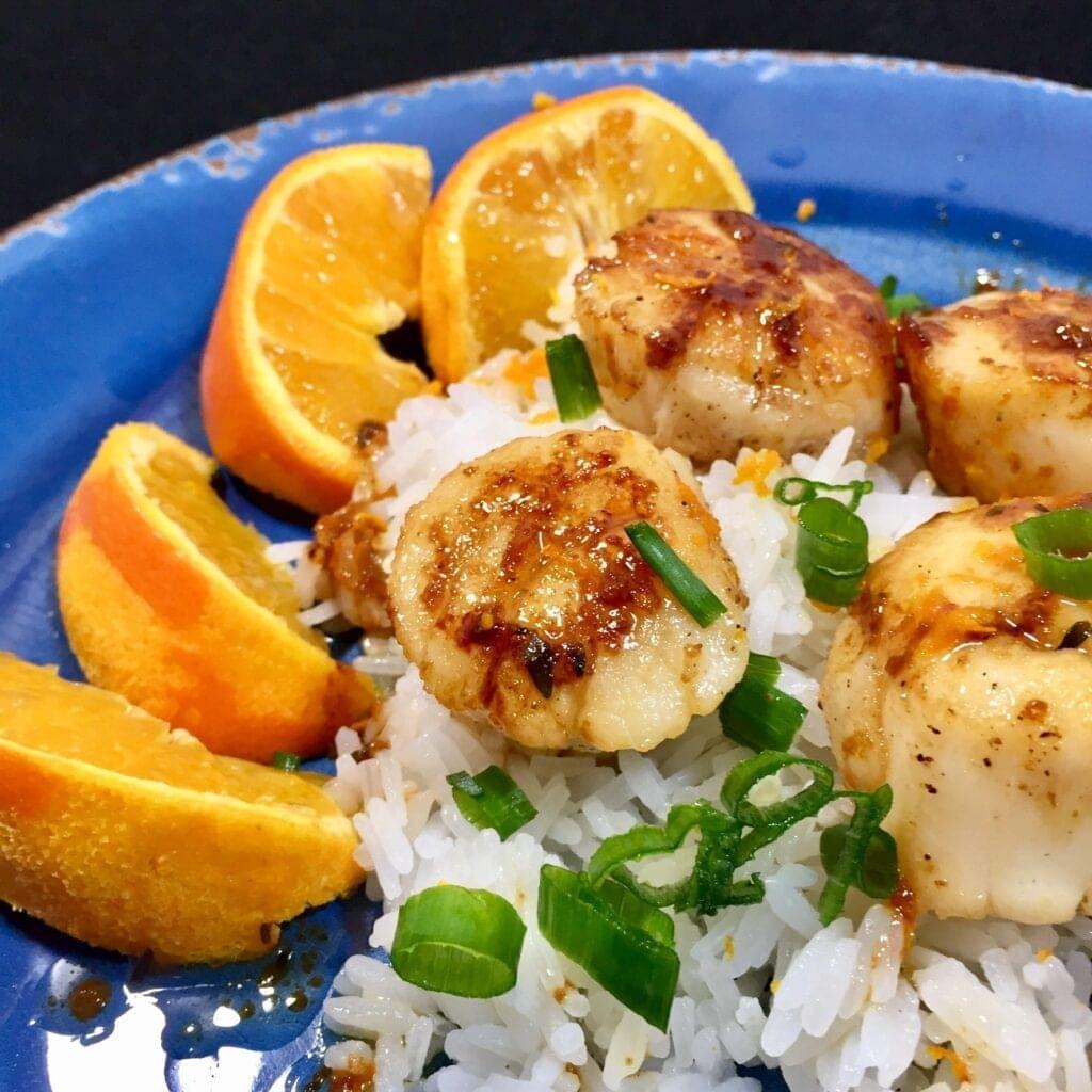 Sauteed sea scallops over rice on a blue plate
