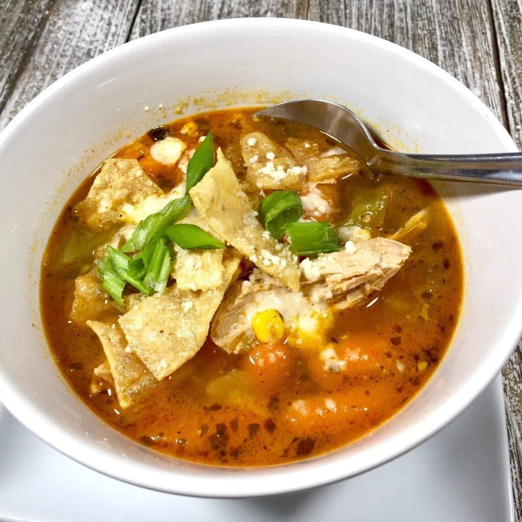 A white bowl of chicken soup with tortillas and Cotija cheese