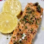 baked salmon fillet with caper sauce and lemons on a white plate