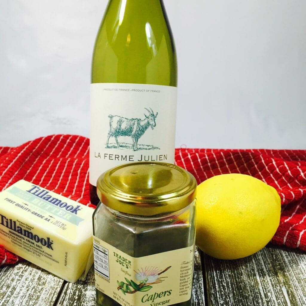 a bottle of wine, capers, butter and lemon on a wooden table