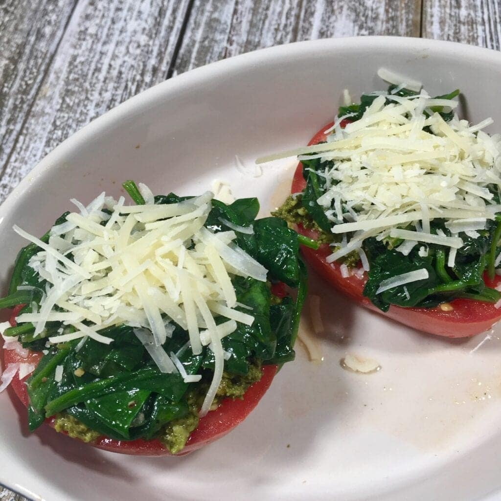 two tomato halves topped with cooked spinach and parmesan cheese in white bowl