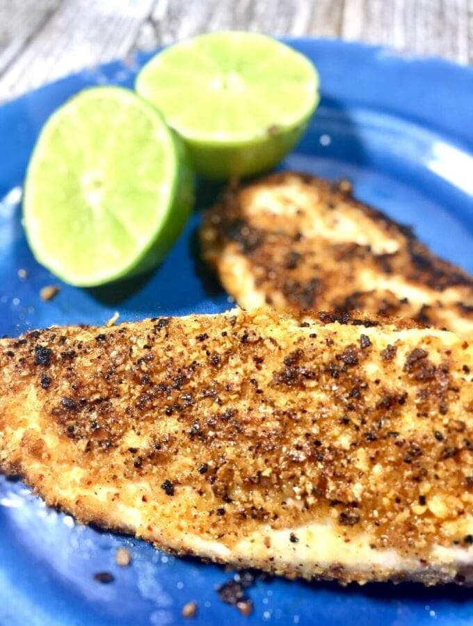two cooked fillets of tilapia on a blue plate with limes