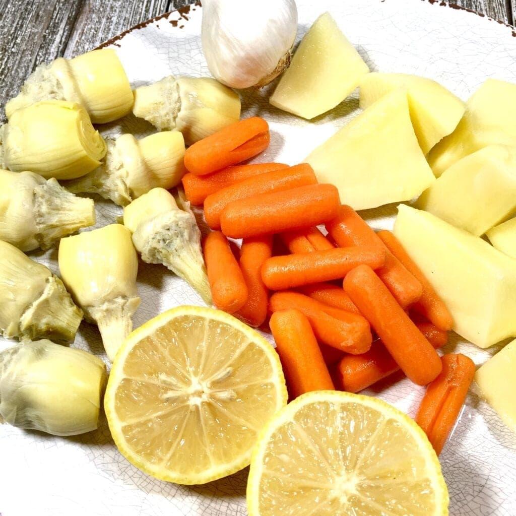 artichokes, lemons, carrots, garlic and potatoes on a white plate