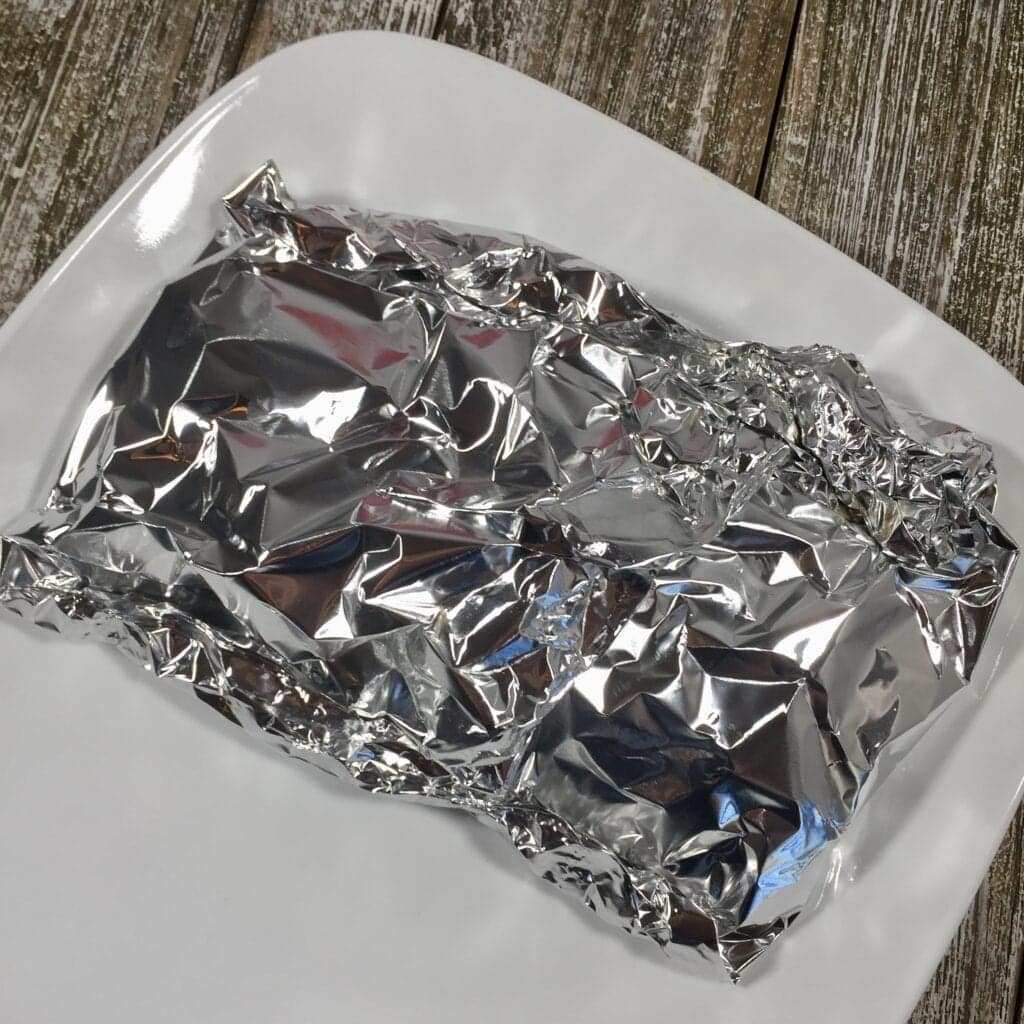 Tin foil package on a white plate