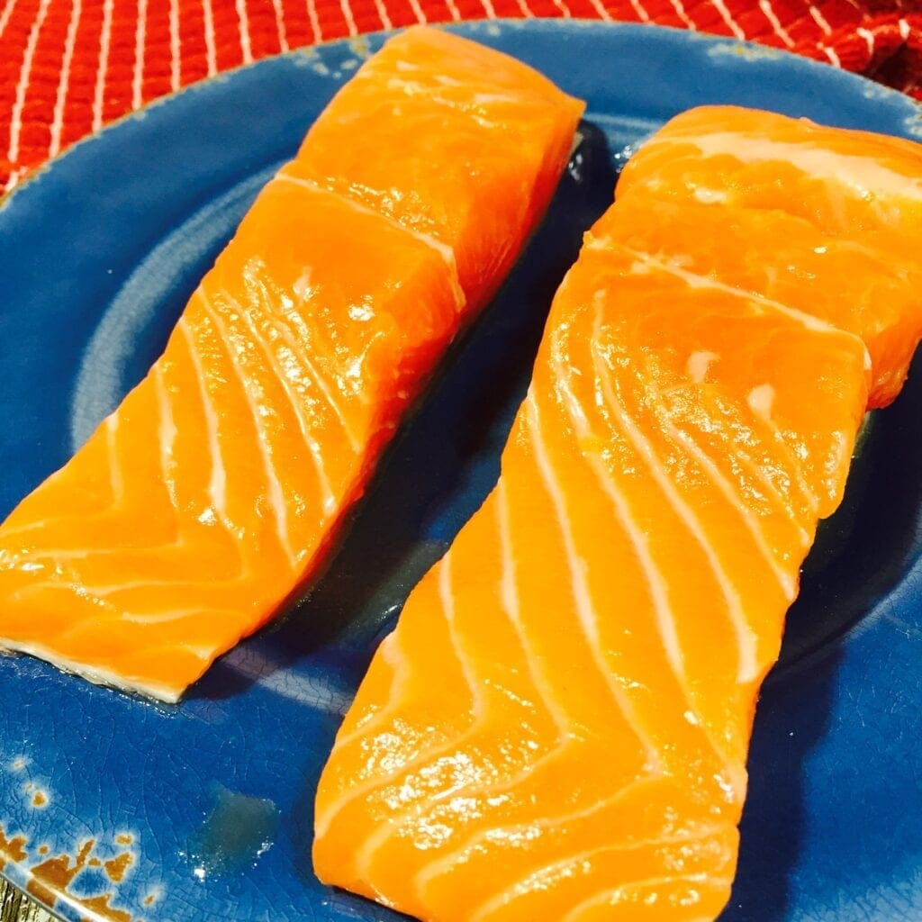 fresh salmon fillets on a blue plate