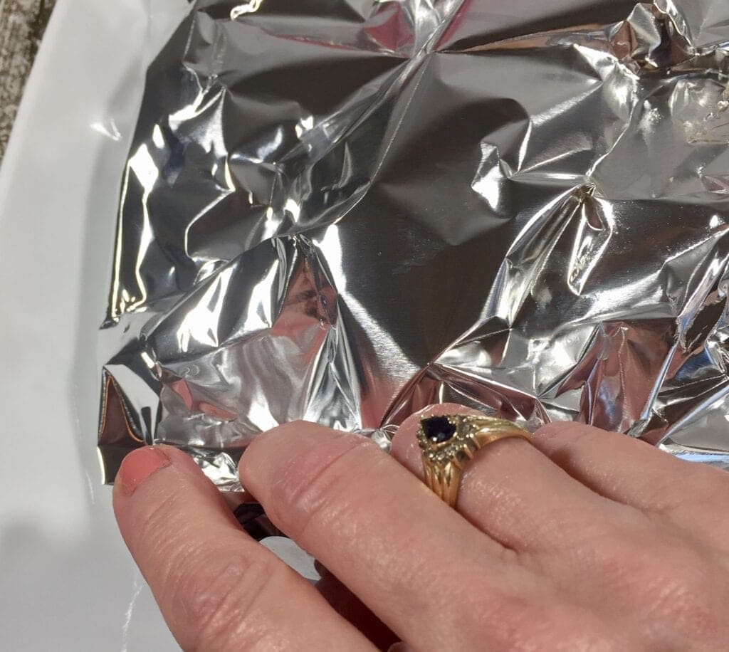 Hand folding a tin foil package