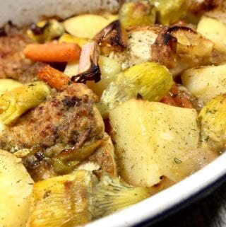 roasted lemon chicken with artichokes, potatoes and carrots in a white pan