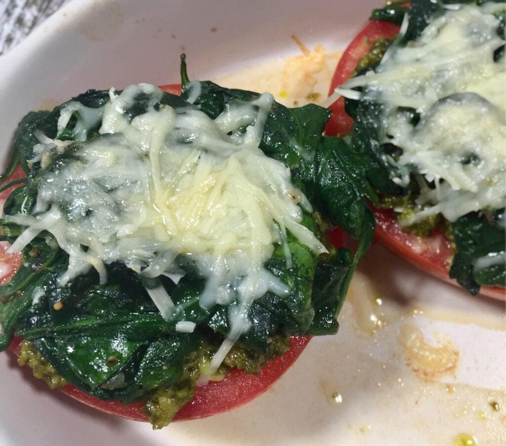 two cooked tomato halves topped with pesto, spinach and parmesan cheese in a white bowl