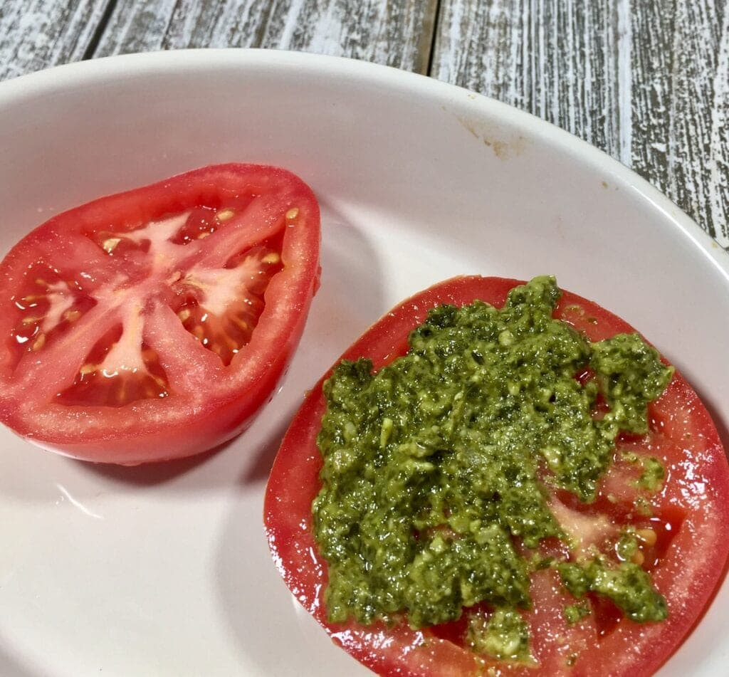 two tomato halves, one with pesto, in a white bowl