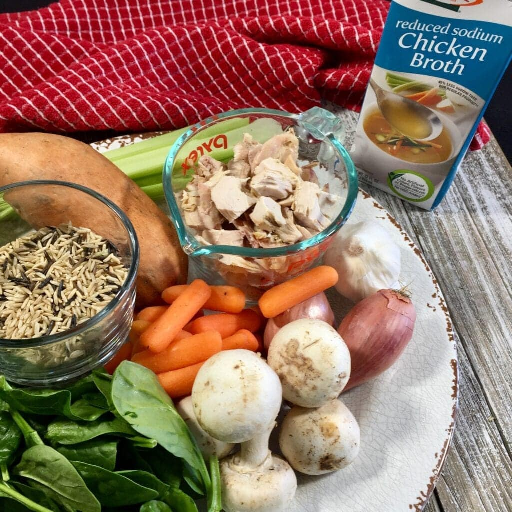 cooked chicken, yam, spinach, wild rice, spinach, carrots, shallots, garlic, celery and mushrooms on a white plate