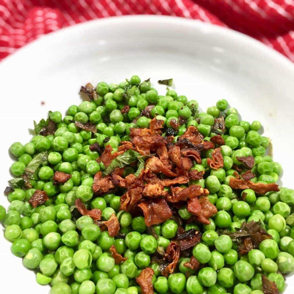 English peas topped with crispy prosciutto in a white bowl