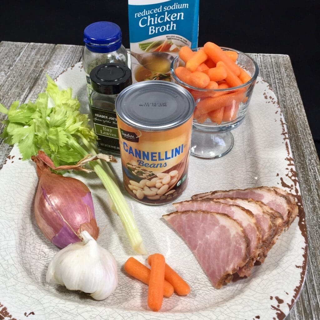 Ingredients of ham, cannellini beans, celery, carrots, garlic and chicken broth on a white platter