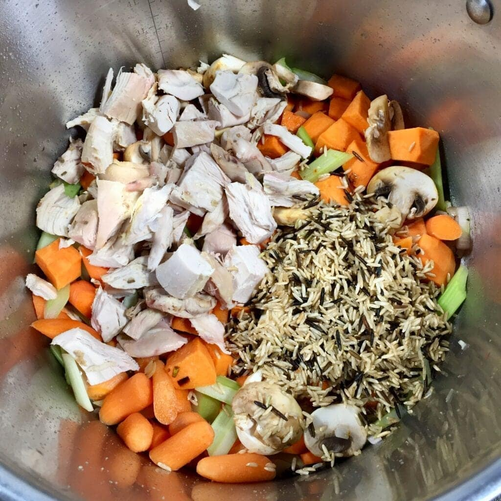mixed vegetables with diced chicken and wild rice in a saute pan