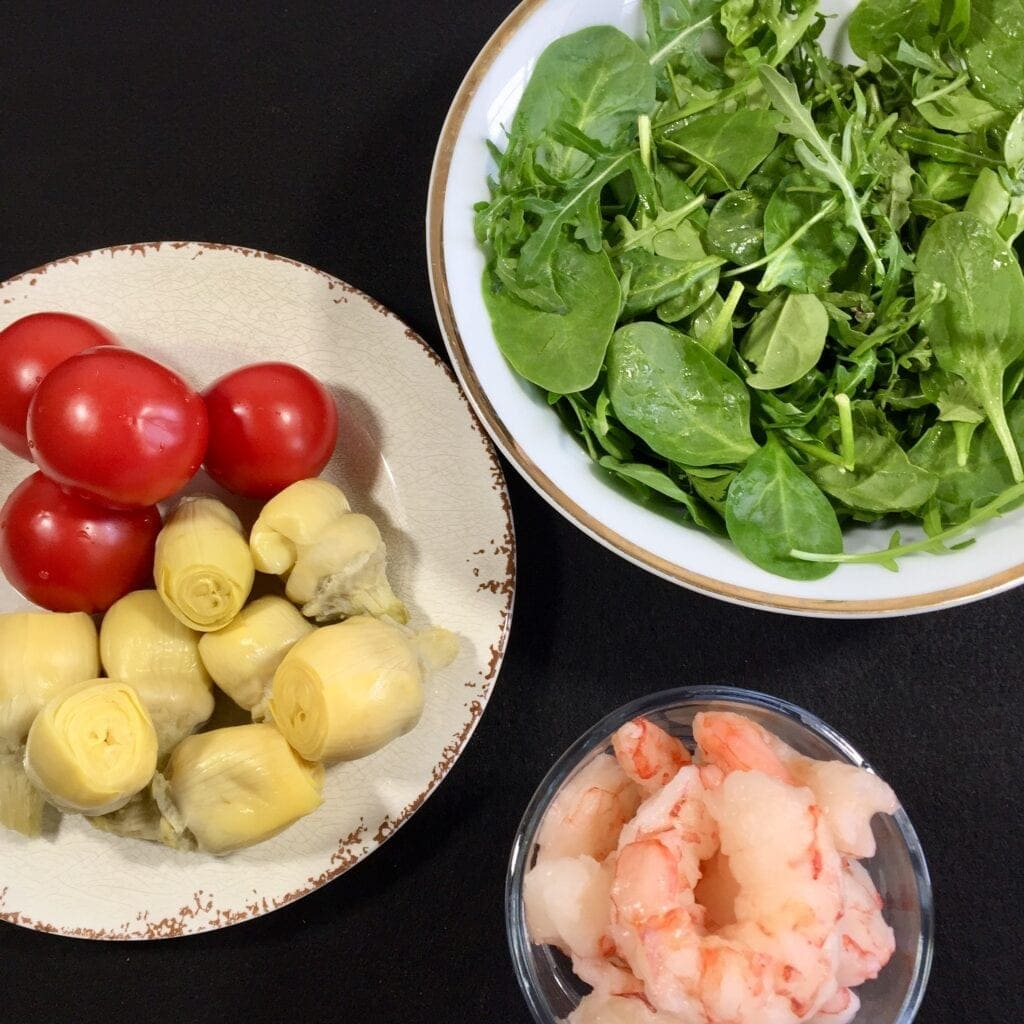 Fresh shrimp, mixed greens, tomatoes and artichoke hearts on a black a=background