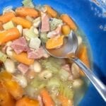 a bowl of Ham and Bean Soup pin a blue bowl with a spoon
