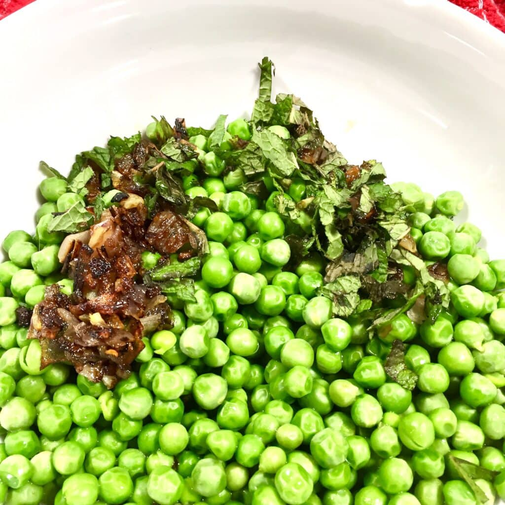 English peas topped with caramelized shallots and mint in a white bowl