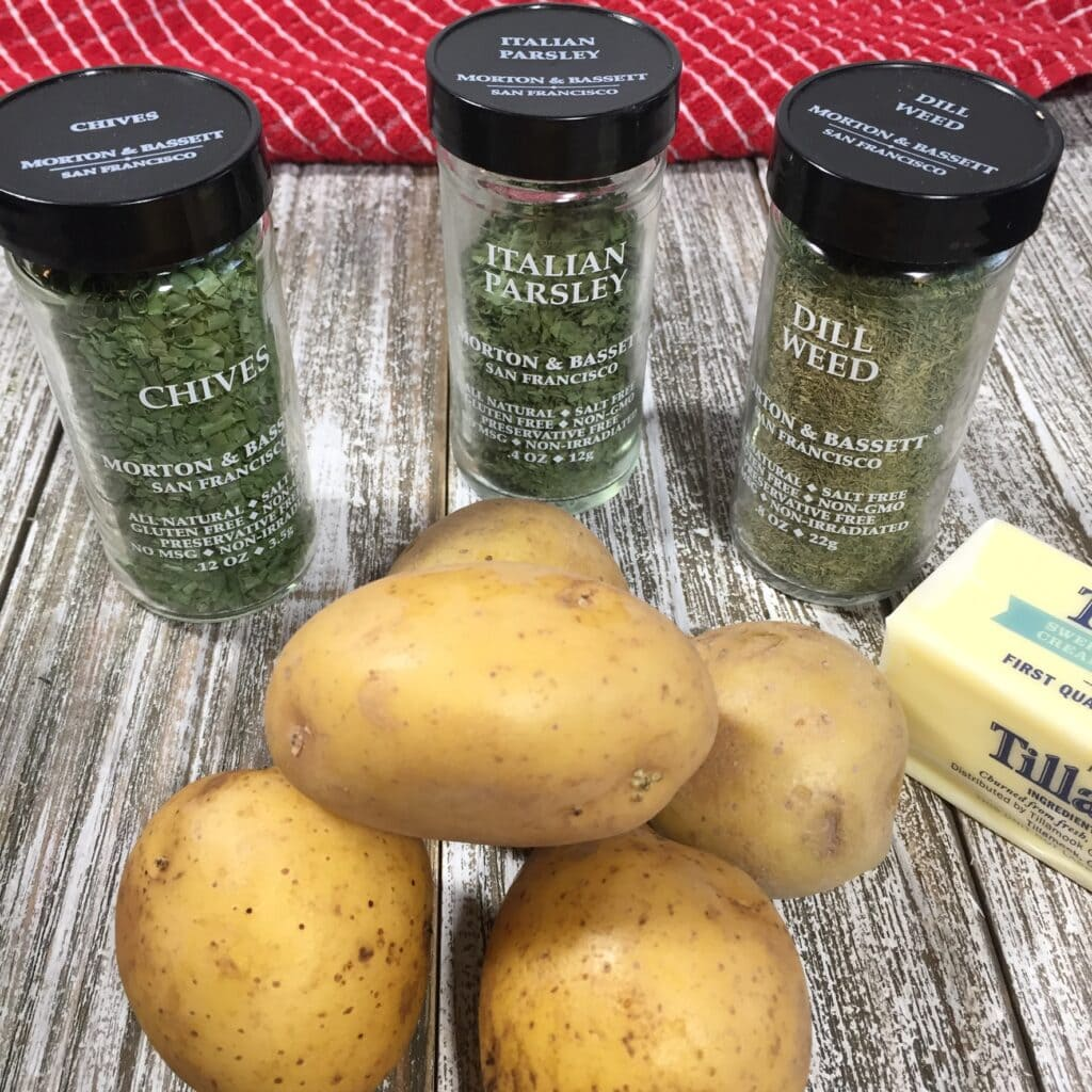 New potatoes with chives, parsley and dill spice bottles on a wooden table