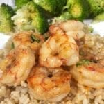Shrimp scampi over brown rice with broccoli on a white plate