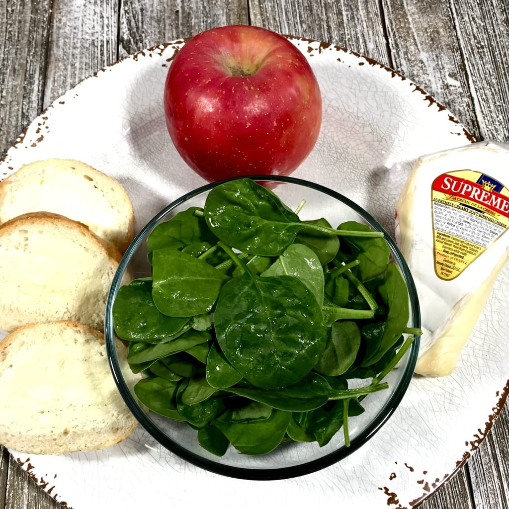 Spinach, baguette slices, brie and a red apple on a white plate