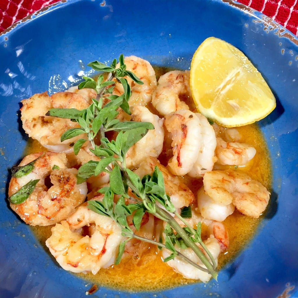Shrimp scampi with lemon slice in a blue bowl