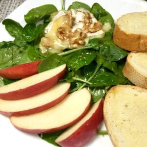 Spinach salad with sliced apples, baguette slices and toasted brie with walnuts on white plate