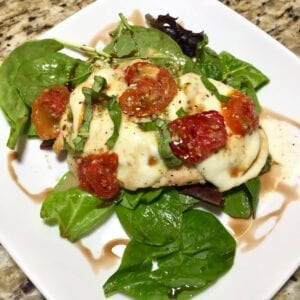 Baked Chicken with melted mozzarella and roasted tomatoes over greens on a white plate
