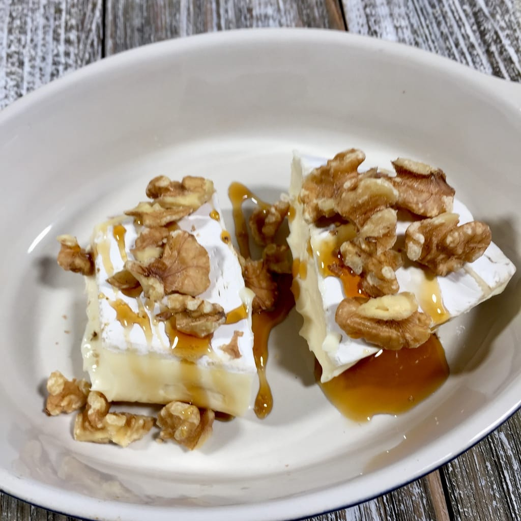 Brie drizzled with honey and topped with walnuts in a white bowl