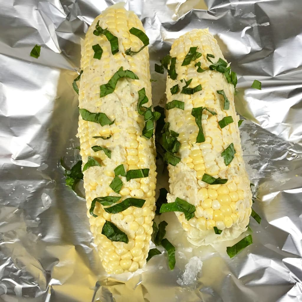 Corn on the cob with butter, parmesan cheese and fresh basil ready to be steamed
