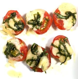 Tomatoes with melted gruyere and basil - Caprese Tomato Bites - on a white plate