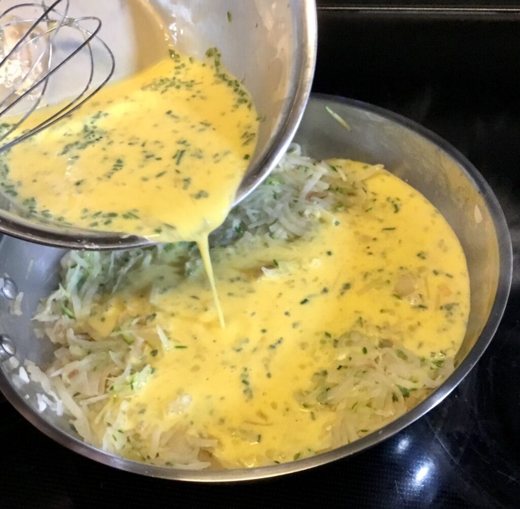Adding whisked eggs to a frypan with shredded zucchini and potatoes