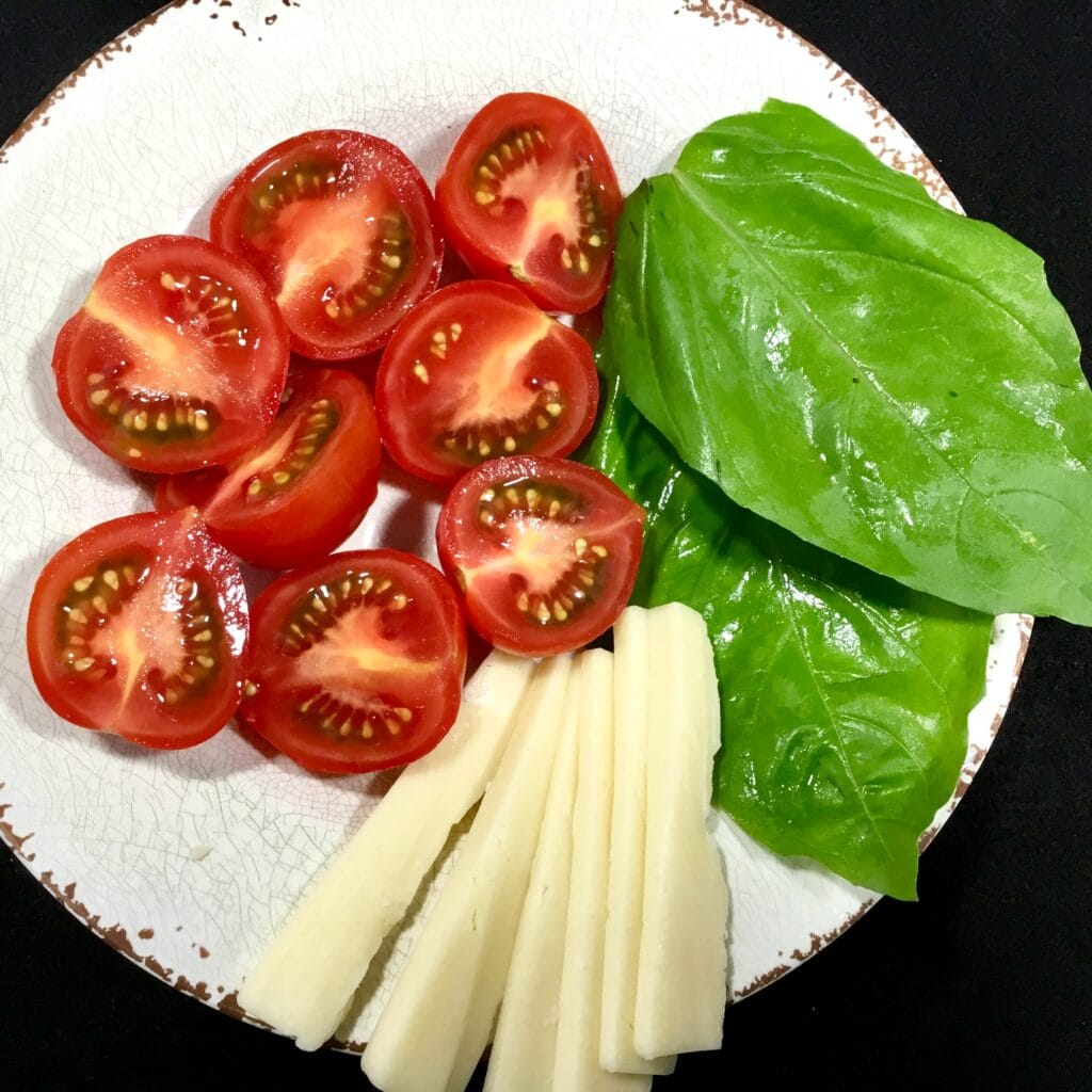 Tomatoes, Basil and Gruyere cheese on a white plate ingredients for Caprese Tomato Bites