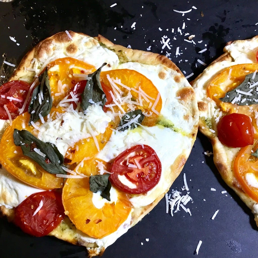 Baked naan pizza with tomatoes, cheese and basil on a black cutting board