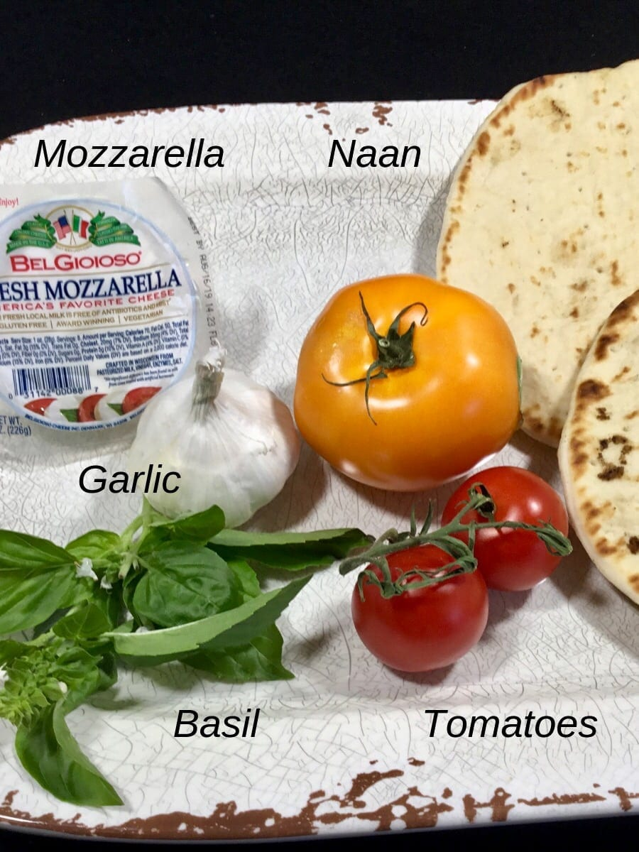 Ingredients for Naan Margherita pizza on a white plate