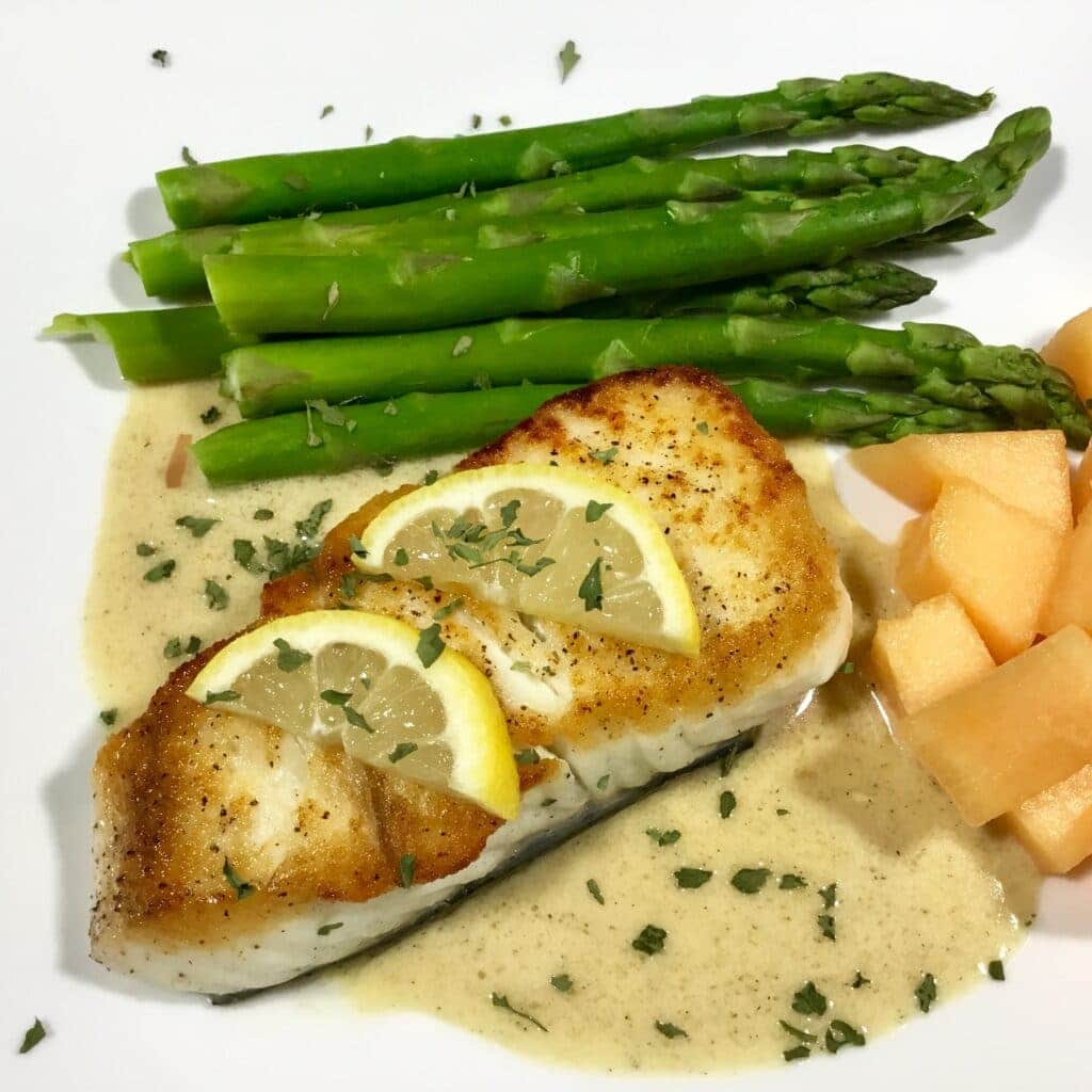 Baked halibut over Tarragon Cream Sauce with asparagus and melons on a white plate