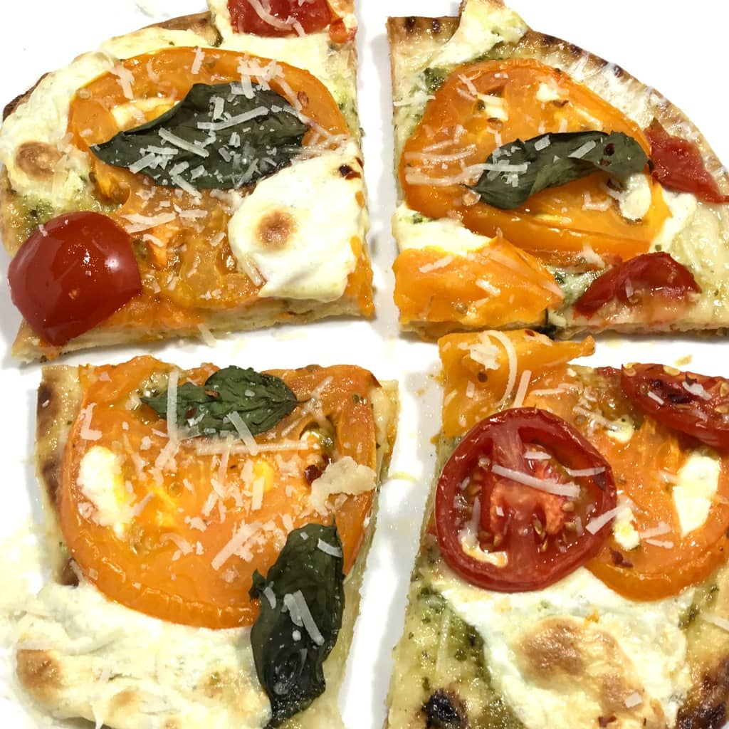 Naan margherita pizza on a white surface