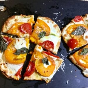 Naan pizza on a black cutting board