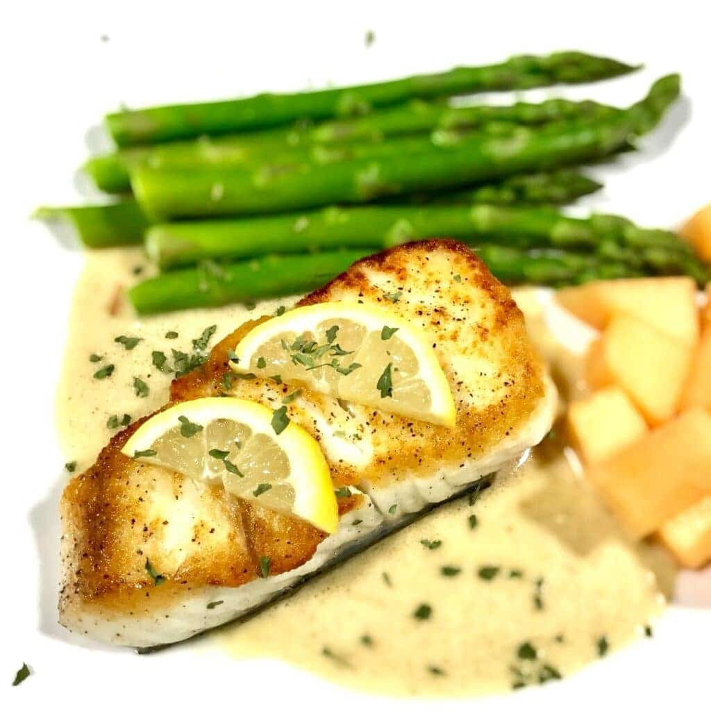 Baked halibut with lemon slices on a bed of tarragon cream sauce